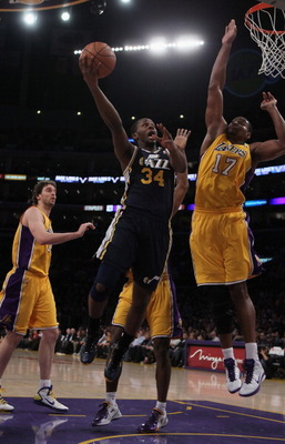 LOS ANGELES, CA - JANUARY 25:  C.J. Miles #34 of the Utah Jazz drives to the basket past Andrew Bynum #17 of the Los Angeles Lakers in the first half at Staples Center on January 25, 2011 in Los Angeles, California. NOTE TO USER: User expressly acknowledg