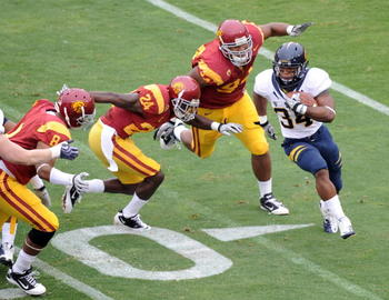 LOS ANGELES, CA - OCTOBER 16:  Shane Vereen #34 of the California Golden Bears is chased by Armond Armstead #94, Shareece Wright #24 and Nick Perry #8 of the USC Trojans during the first quarter at Los Angeles Memorial Coliseum on October 16, 2010 in Los