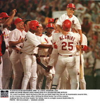 SLP98090819- 08 SEPTEMBER 1998- ST. LOUIS, MISSOURI, USA: St. Louis Cardinals'' Mark McGwire lifts his son Matt high into the air as teammates swarm him, as he crosses home plate after hitting his 62nd home run of the season, making him the all time leade