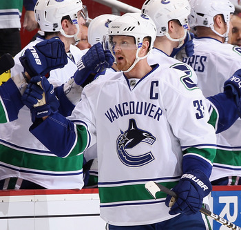 GLENDALE, AZ - MARCH 08:  Henrik Sedin #33 of the Vancouver Canucks celebrates with teammates on the bench after scoring a second period goal against the Phoenix Coyotes during the NHL game at Jobing.com Arena on March 8, 2011 in Glendale, Arizona.  (Phot