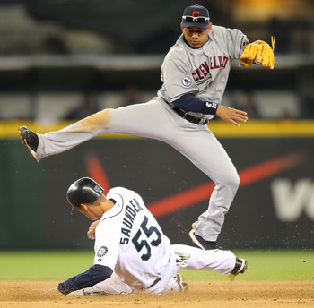 SEATTLE - APRIL 10:  Second baseman Orlando Cabrera #20 of the Cleveland Indians hops over Michael Saunders #55 of the Seattle Mariners on a double play in the fifth inning at Safeco Field on April 10, 2011 in Seattle, Washington. (Photo by Otto Greule Jr