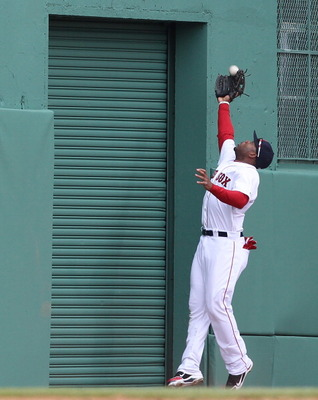 BOSTON, MA - APRIL 8:  Carl Crawford #13 of the Boston Red Sox snags a fly ball against the New York Yankees during Opening Day at Fenway Park on April 8, 2011 in Boston, Massachusetts. (Photo by Jim Rogash/Getty Images)