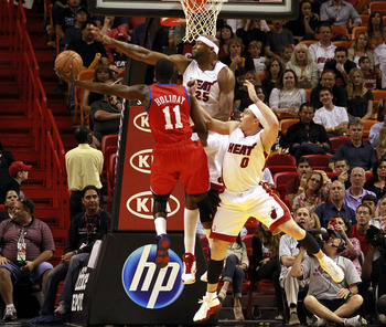 MIAMI, FL - MARCH 25:  Center Erick Dampier #25 and guard Mike Bibby #0 of the Miami Heat defend against Forward Jrue Holiday #11 of the Philadelphia 76ers at American Airlines Arena on March 25, 2011 in Miami, Florida. The Heat defeated the Sixers 111-99