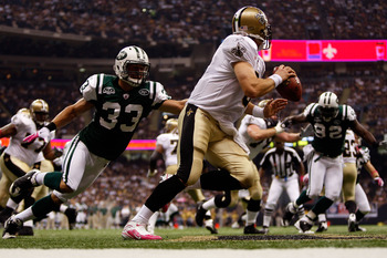 NEW ORLEANS - OCTOBER 04:  Drew Brees #9 of the New Orleans Saints avoids a tackle by Eric Smith #33 of the New York Jets at the Louisana Superdome on October 4, 2009 in New Orleans, Louisiana.  (Photo by Chris Graythen/Getty Images)