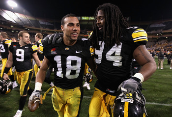 TEMPE, AZ - DECEMBER 28:  Defensive player of the game Micah Hyde #18 and Adrian Clayborn #94 of the Iowa Hawkeyes walk off the field after defeating the Missouri Tigers in the Insight Bowl at Sun Devil Stadium on December 28, 2010 in Tempe, Arizona. The