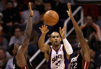 PHOENIX - DECEMBER 23:  Grant Hill #33 of the Phoenix Suns passes the ball under pressure from LeBron James #6 and James Jones #22 of the Miami Heat during the NBA game at US Airways Center on December 23, 2010 in Phoenix, Arizona. The Heat defeated the S