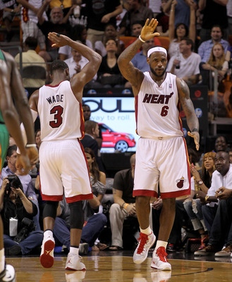 MIAMI, FL - APRIL 10:  LeBron James #6 and Dwyane Wade #3 of the Miami Heat high five during a game against the Boston Celtics at American Airlines Arena on April 10, 2011 in Miami, Florida. NOTE TO USER: User expressly acknowledges and agrees that, by do