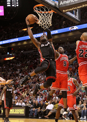 MIAMI, FL - MARCH 06:  Dwyane Wade #3 of the Miami Heat shoots over Luol Deng #9 of the Chicago Bulls during a game at American Airlines Arena on March 6, 2011 in Miami, Florida. NOTE TO USER: User expressly acknowledges and agrees that, by downloading an