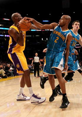 LOS ANGELES, CA - JANUARY 7:   Jarrett Jack #2 of the New Orleans Hornets gets a hand on the ball as he defends against Lamar Odom #7 of the Los Angeles Lakers at Staples Center on January 7, 2011 in Los Angeles, California.  The Lakers won 101-97.  NOTE