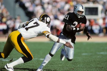 LOS ANGELES, CA - JANUARY 1:  Cliff Branch #21 of the Los Angeles Raiders runs the ball against Mel Blount #47 of the Pittsburgh Steelers during the AFC Divisional playoff game at the Los Angeles Memorial Coliseum on January 1, 1984 in Los Angeles, Califo