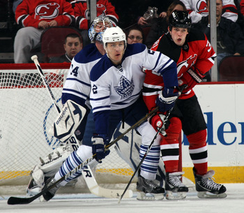 NEWARK, NJ - APRIL 06: Luke Schenn #2 of the Toronto Maple Leafs and Nick Palmieri #32 of the New Jersey Devils battle in front of the net at the Prudential Center on April 6, 2011 in Newark, New Jersey.  (Photo by Bruce Bennett/Getty Images)