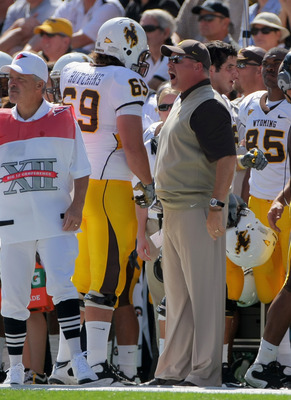 BOULDER, CO - SEPTEMBER 19:  Head coach Dave Christensen of the Wyoming Cowboys has words with right tackle John Hutchins #69 after he was called for illegal motion against the Colorado Buffaloes at Folsom Field on September 19, 2009 in Boulder, Colorado.