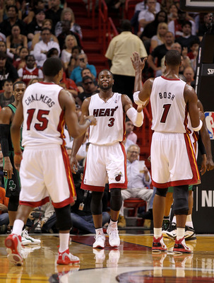 MIAMI, FL - APRIL 10:  Dwyane Wade #3 of the Miami Heat high fives with Chris Bosh #1 and Mario Chalmers #15 during a game against the Boston Celtics at American Airlines Arena on April 10, 2011 in Miami, Florida. NOTE TO USER: User expressly acknowledges