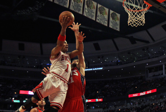 CHICAGO, IL - APRIL 13: Derrick Rose #1 of the Chicago Bulls puts up a shot against Brook Lopez #11 of the New Jersey Nets at the United Center on April 13, 2011 in Chicago, Illinois. The Bulls defeated the Nets 97-92. NOTE TO USER: User expressly acknowl