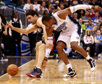 ORLANDO, FL - DECEMBER 06:  Dwight Howard #12 of the Orlando Magic and Zaza Pachulia #27 of the Atlanta Hawks battle for a loose ball during the game at Amway Arena on December 6, 2010 in Orlando, Florida. NOTE TO USER: User expressly acknowledges and agr