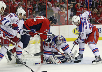 WASHINGTON, DC - APRIL 13:  Henrik Lundqvist #30 of the New York Rangers makes the save as Mike Knuble #22 of the Washington Capitals flies past him in Game One of the Eastern Conference Quarterfinals during the 2011 NHL Stanley Cup Playoffs at Verizon Ce