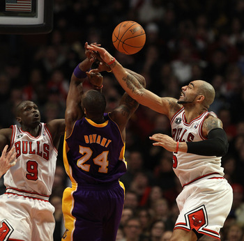 CHICAGO, IL - DECEMBER 10: Carlos Boozer #5 of the Chicago Bulls knocks the ball away from Kobe Bryant #24 of the Los Angeles Lakers as Luol Deng #9 also defends at the United Center on December 10, 2010 in Chicago, Illinois. The Bulls defeated the Lakers