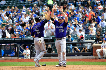Ian Stewart and Jason Giambi celebrate after scoring the go-ahead runs on a double off the bat of backup catcher Jose Morales in a 6-5 Rockies victory over the Mets