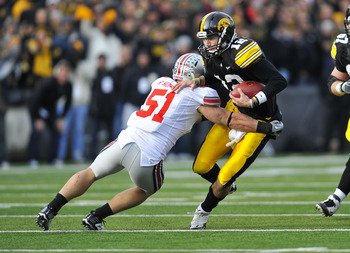 IOWA CITY, IA - NOVEMBER 20:  Quarterback Ricky Stanzi #12 of the University of Iowa Hawkeyes scrambles for yards as linebacker Ross Homan #51 of the Ohio State Buckeyes defends during the first half of play at Kinnick Stadium on November 20, 2010 in Iowa