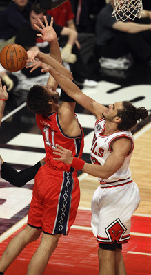 CHICAGO, IL - APRIL 13: Joakim Noah #13 of the Chicago Bulls blocks a shot by Brook Lopez #11 of the New Jersey Nets as Carlos Boozer #5 reaches for the ball at United Center on April 13, 2011 in Chicago, Illinois. NOTE TO USER: User expressly acknowledge