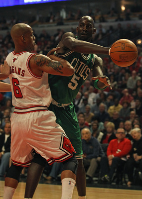 CHICAGO, IL - APRIL 07: Kevin Garnett #5 of the Boston Celtics passes the ball around Keith Bogans #6 of the Chicago Bulls at United Center on April 7, 2011 in Chicago, Illinois. NOTE TO USER: User expressly acknowledges and agress that, by downloading an