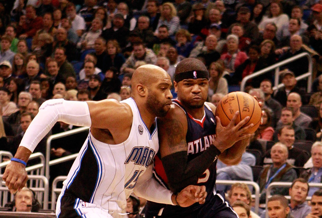 ORLANDO, FL - DECEMBER 06:  Josh Smith #5 of the Atlanta Hawks drives against Vince Carter#15 of the Orlando Magic during the game at Amway Arena on December 6, 2010 in Orlando, Florida. NOTE TO USER: User expressly acknowledges and agrees that, by downlo