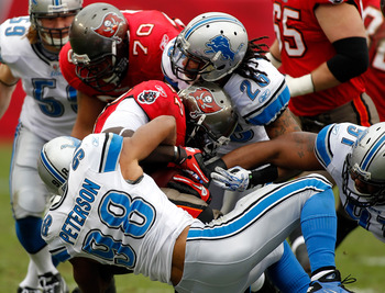 TAMPA, FL - DECEMBER 19:  Running  back LeGarrette Blount #27 of the Tampa Bay Buccaneers is tackled by defensive tackle Julian Peterson #98 of the Detroit Lions during the game at Raymond James Stadium on December 19, 2010 in Tampa, Florida.  (Photo by J