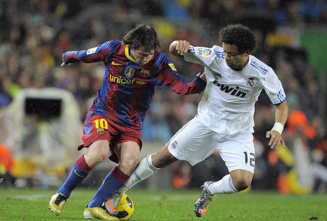 BARCELONA, SPAIN - NOVEMBER 29:  Lionel Messi of Barcelona (L) takes the ball past Marcelo Vieira of Real Madrid during the La Liga match between Barcelona and Real Madrid at the Camp Nou Stadium on November 29, 2010 in Barcelona, Spain.  Barcelona won th