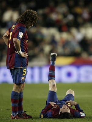 VALENCIA, SPAIN - DECEMBER 15:  Carles Puyol (L) of Barcelona looks at his injured teammate Lionel Messi laying on the pitch before abandoning the match during the La Liga match between Valencia and Barcelona at the Mestalla Stadium December 15, 2007 in V