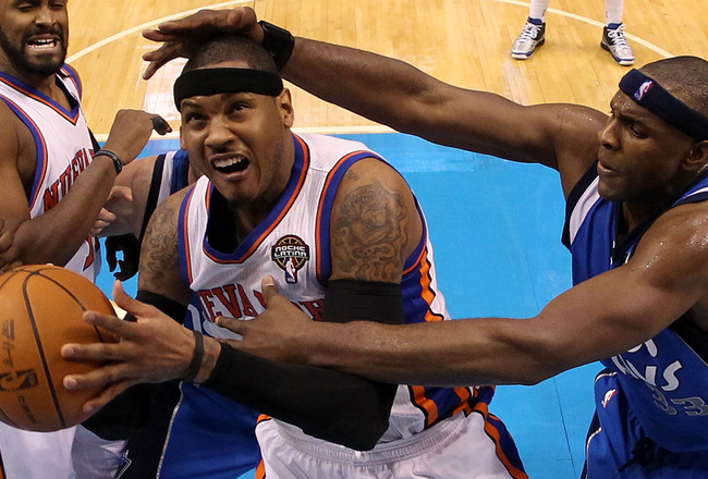 DALLAS, TX - MARCH 10:  Forward Carmelo Anthony #7 of the New York Knicks is fouled by Brendan Haywood #33 of the Dallas Mavericks at American Airlines Center on March 10, 2011 in Dallas, Texas.  NOTE TO USER: User expressly acknowledges and agrees that,