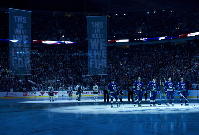 VANCOUVER, CANADA - APRIL 15: The Vancouver Canucks and the Chicago Blackhawks stand on their respective blue lines for the singing of the national anthems prior to the start of Game Two of the Western Conference Quarterfinals during the 2011 NHL Stanley