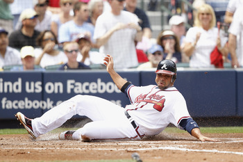 ATLANTA, GA - APRIL 9: Alex Gonzalez #2 of the Atlanta Braves slides at home plate to score a run against the Philadelphia Phillies at Turner Field on April 9, 2011 in Atlanta, Georgia. The Phillies won 10-2. (Photo by Joe Robbins/Getty Images)