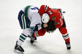 CHICAGO - MARCH 29: Duncan Keith #2 of the Chicago Blackhawks and Alex Burrows #14 of the Vancouver Canucks fight in the third period on March 29, 2009 at the United Center in Chicago, Illinois. The Canucks defeated the Blackhawks 4-0. (Photo by Jonathan