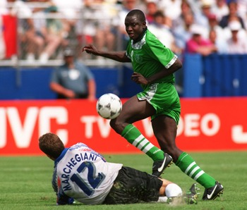 5 JULY 1994:  RASHEED YEKINI OF NIGERIA DRIBBLES AROUND THE FALLEN LUCA MARCHESIANI OF ITALY DURING THEIR SECOND ROUND MATCH IN THE 1994 WORLD CUP AT FOXBORO STADIUM IN MASSACHUSETTS.  ITALY WON THE GAME, 2-1, IN EXTRA TIME. Mandatory Credit: Shaun Botter