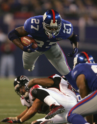 EAST RUTHERFORD, NJ - NOVEMBER 21:  Running back Ron Dayne #27 of the New York Giants is hit by cornerback DeAngelo Hall #21 of the Atlanta Falcons in the third quarter at Giants Stadium on November 21, 2004 in East Rutherford, New Jersey.  The Falcons de