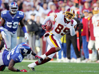 LANDOVER, MD - DECEMBER 24:  Santana Moss #89 of the Washington Redskins breaks a tackle from Will Allen #25 of the New York Giants and heads for the endzone to score his third touchdown of the day on December 24, 2005 at FedEx Field in Landover, Maryland