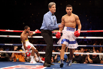 LAS VEGAS - DECEMBER 11:  (R-L) Victor Ortiz walks back to his corner with referee Vic Drakulich after Ortiz knocks down Lamont Petersen in the third round during the super lightweight fight at Mandalay Bay Events Center on December 11, 2010 in Las Vegas,
