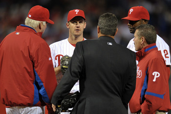 PHILADELPHIA, PA - APRIL 15: Starting pitcher Roy Oswalt #44 of the Philadelphia Phillies meets on the mound with manager Charlie Manuel, home plate umpire Rob Drake, Ryan Howard #6 and a trainer about an injury he suffered during the game against the Flo