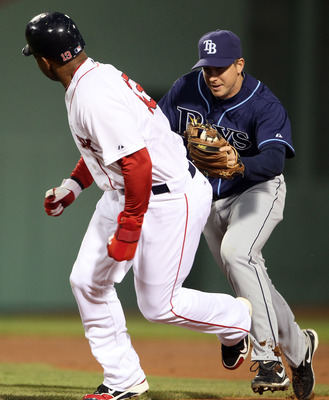 BOSTON, MA - APRIL 12:  Carl Crawford #13 of the Boston Red Sox is tagged by Elliot Johnson #9 of the Tampa Bay Rays on April 12, 2011 at Fenway Park in Boston, Massachusetts.  (Photo by Elsa/Getty Images)