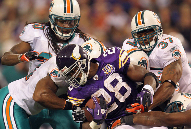MINNEAPOLIS - SEPTEMBER 19:  Adrian Peterson #28 of the Minnesota Vikings carries the ball as he is tackled by the Miami Dolphins defense during the first half of the game on September 19, 2010 at Hubert H. Humphrey Metrodome in Minneapolis, Minnesota.  (