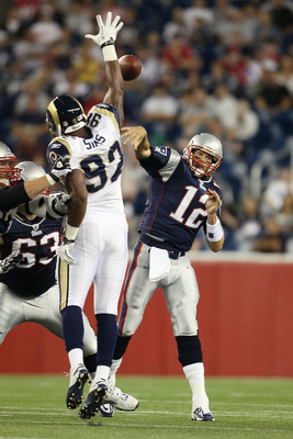 FOXBORO, MA - AUGUST 26:  Tom Brady #12 of the New England Patriots passes the ball under pressure from Eugene Sims #92 of the St. Louis Rams on August 26, 2010 at Gillette Stadium in Foxboro, Massachusetts.  (Photo by Elsa/Getty Images)