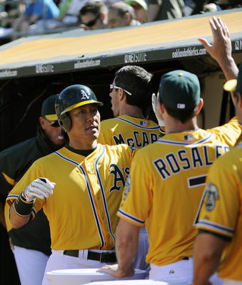 OAKLAND, CA - APRIL 3: Hideki Matsui #55 of the Oakland Athletics gets a high-fives from teammates in the dougout after scoring a run against the Seattle Mariners during a MLB baseball game at the Oakland-Alameda County Coliseum April 3, 2011 in Oakland,