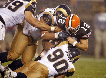 CLEVELAND - AUGUST 21:  C.J. Ah You #99, Ernest Reid #62 and Hall Davis #90 of the St. Louis Rams tackle Colt McCoy #12 of the Cleveland Browns at Cleveland Browns Stadium on August 21, 2010 in Cleveland, Ohio.  (Photo by Matt Sullivan/Getty Images)