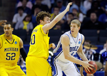 CHARLOTTE, NC - MARCH 20:  Mason Plumlee #5 of the Duke Blue Devils looks to pass against Zack Novak #0 of the Michigan Wolverines during the third round of the 2011 NCAA men's basketball tournament at Time Warner Cable Arena on March 20, 2011 in Charlott