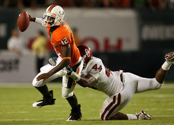 FORT LAUDERDALE, FL - OCTOBER 03: Quarterback Jacory Harris #12 of the Miami Hurricanes is sacked by defensive end Jeremy Beal #44 of the Oklahoma Sooners at Land Shark Stadium on October 3, 2009 in Fort Lauderdale, Florida. Miami defeated Oklahoma 21-20.