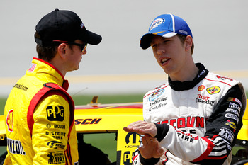 TALLADEGA, AL - APRIL 16:  Kurt Busch (L), driver of the #22 Shell/Pennzoil-AAA Dodge, talks with Brad Keselowski (R), driver of the #2 Miller Lite Dodge, on the grid during qualifying for the NASCAR Sprint Cup Series Aaron's 499 at Talladega Superspeedwa