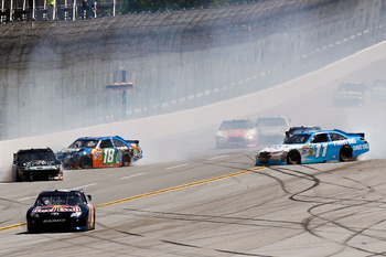 TALLADEGA, AL - APRIL 17:  Kyle Busch, driver of the #18 M&M's Pretzel Toyota, Denny Hamlin, driver of the #11 FedEx Office Toyota, and Matt Kenseth, driver of the #17 Crown Royal Black Ford, spin out after an incident in the NASCAR Sprint Cup Series Aaro