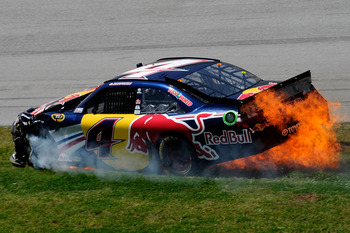 TALLADEGA, AL - APRIL 17:  Kasey Kahne, driver of the #4 Red Bull Toyota, slides through the grass while on fire after an incident in the NASCAR Sprint Cup Series Aaron's 499 at Talladega Superspeedway on April 17, 2011 in Talladega, Alabama.  (Photo by J