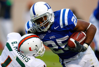 DURHAM, NC - OCTOBER 18:  Running back Tony Jackson #25 of the Duke Blue Devils stiff arms Brandon Harris #1 of the Miami Hurricanes during the game at Wallace Wade Stadium on October 18, 2008 in Durham, North Carolina.  (Photo by Kevin C. Cox/Getty Image