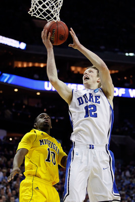 CHARLOTTE, NC - MARCH 20:  Kyle Singler #12 of the Duke Blue Devils goes up for a shot against Tim Hardaway Jr. #10 of the Michigan Wolverines in the first half during the third round of the 2011 NCAA men's basketball tournament at Time Warner Cable Arena